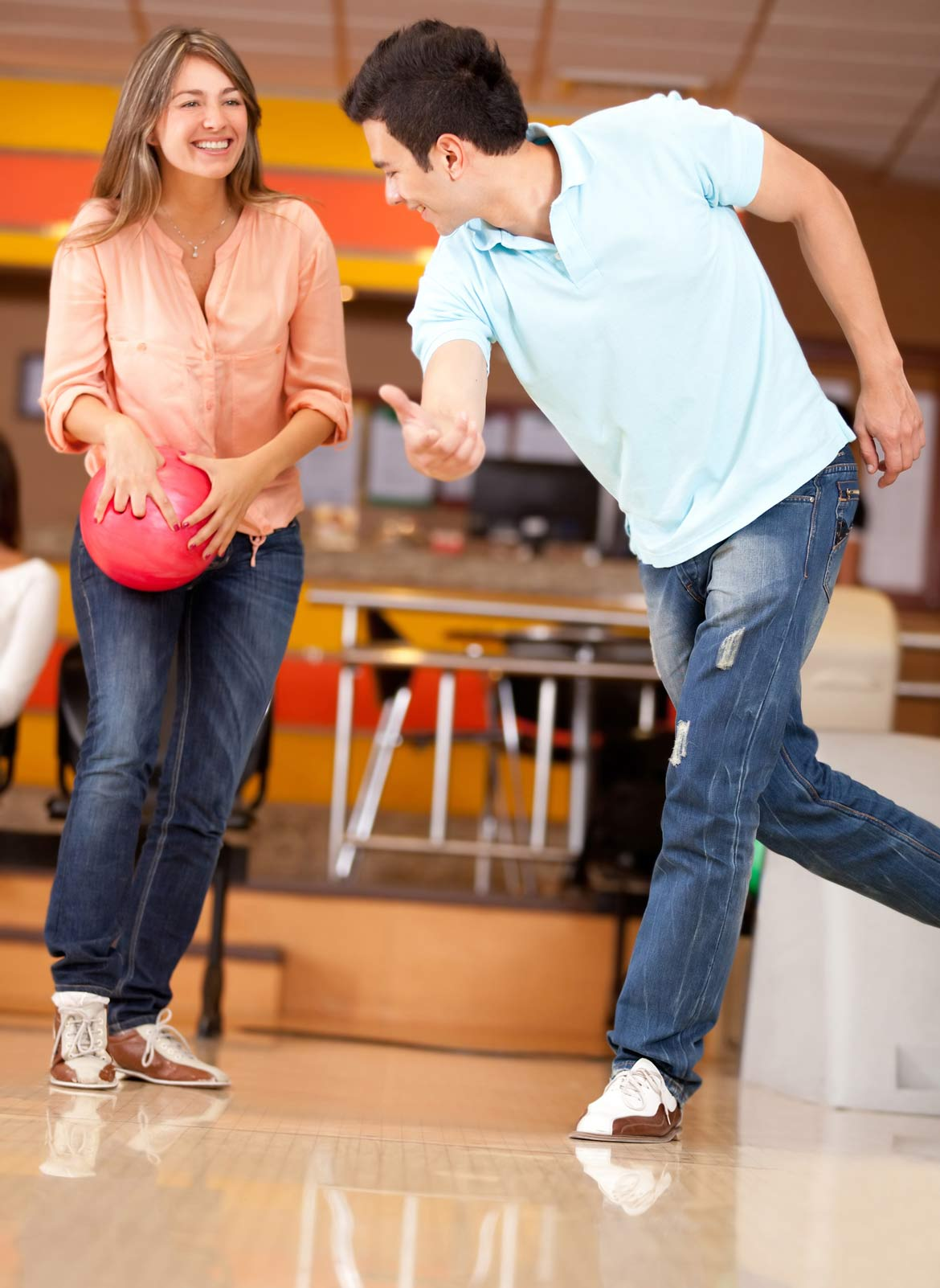 A man showing a woman how to play bowling